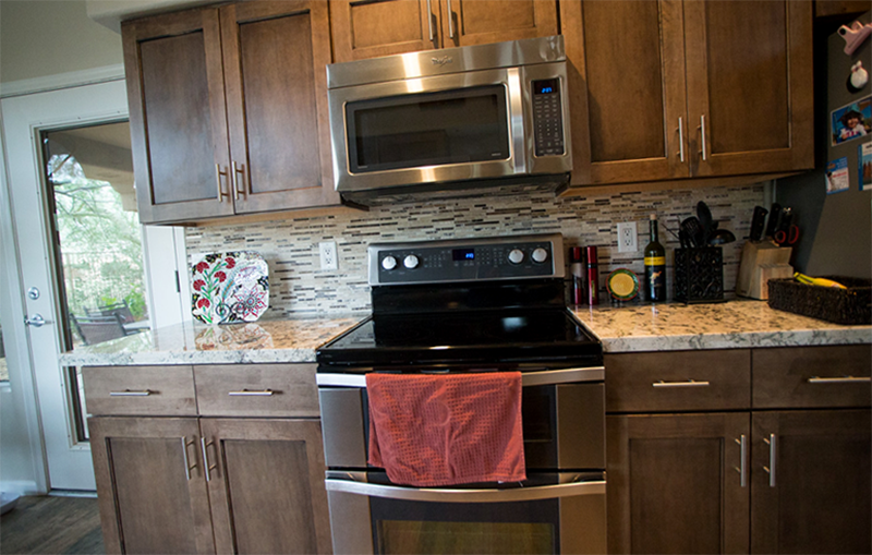 Arizona Granite paired with brown cabinet with gas range and a oven