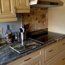 Granite counter top Juparana Sunset complementing beige kitchen cabinets
